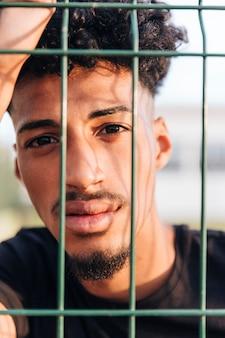 フェンスの後ろにクールな民族の若い男をトリミング