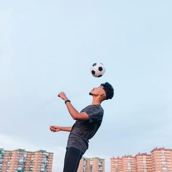 Тренировка мыжского спортсмена с футбольным мячом против голубого неба