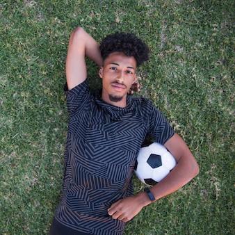 芝生の上で一時停止中に背中に横になっているリラックスしたスポーツマン
