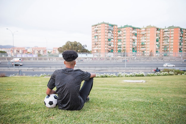 Спортсмен сидит на траве в городской среде