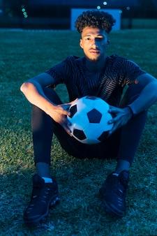 スポーツマンは草の上に座って、夕暮れ時にサッカーを保持