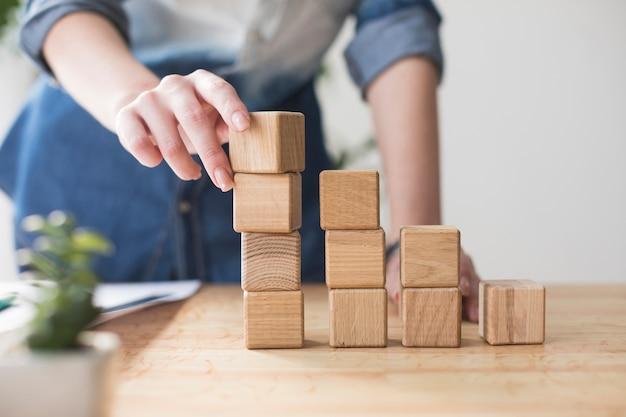Конец-вверх женской руки штабелируя деревянный блок на столе на офисе