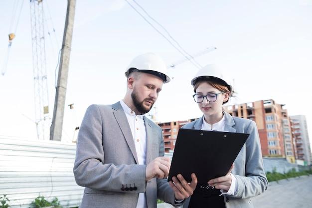 クリップボードを見てハード帽子をかぶっている若い女性と男性の建築家
