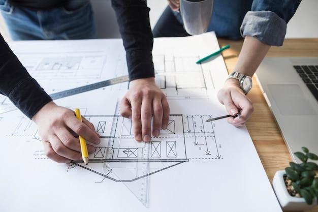 建築家の手で事務所の木製の机の上の青写真に取り組んで