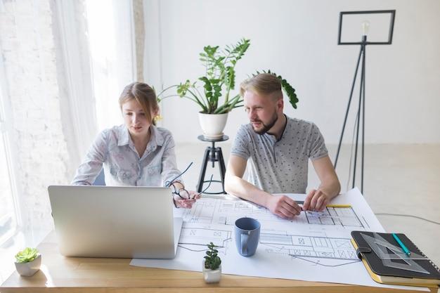 若い男が職場で彼女の同僚を使用してラップトップを見て