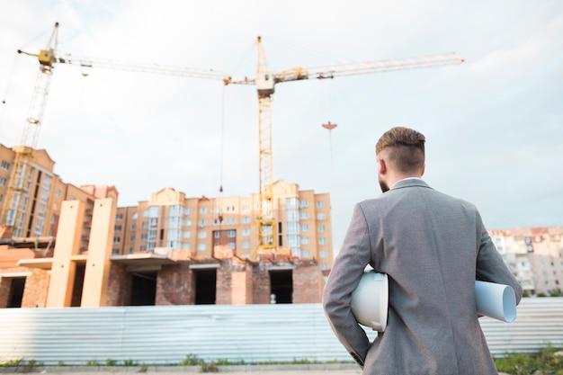 青写真と工事現場を見てヘルメットを保持している男性建築家の背面図