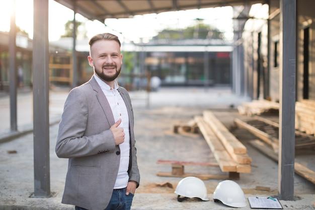 カメラを見てジェスチャーを親指を示す笑みを浮かべて若い建築家男の肖像