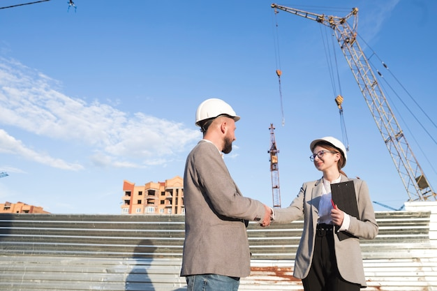 Два профессиональных инженера пожимают руку на строительной площадке