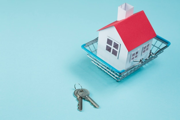 青い表面上のキーを持つ金属製のバスケットの赤い屋根の家モデル