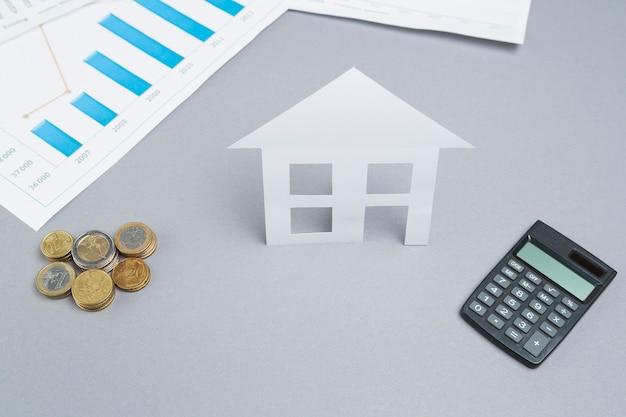 Сложенные монеты и бумажный вырез дома с калькулятором на рабочем столе