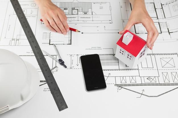 Женская рука держит модель дома над планом в офисе