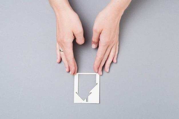灰色の背景上の家の切り欠きに触れる女性の手の高角度のビュー