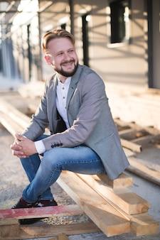 屋外で木の板に座っている若い男の笑みを浮かべてください。