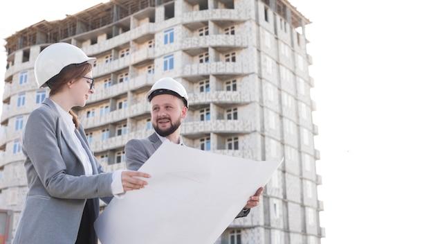 Два профессиональных улыбающихся инженерных холдинга план и глядя друг на друга