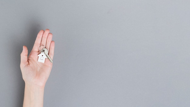 灰色の背景上の家の鍵を持っている人間の手の上から見る