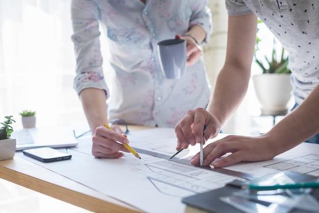 建築手のクローズアップのオフィスで木製のテーブルの上の青写真に取り組んで
