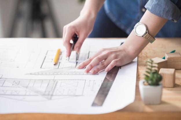 職場で木製の机の上の青写真に取り組んでいる女性の手のクローズアップ