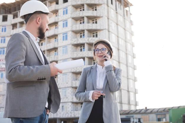 Улыбается женщина разговаривает по мобильному телефону, а ее коллеги, глядя друг на друга