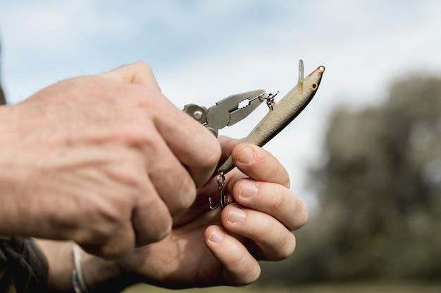 Человек, чинящий рыболовный крючок