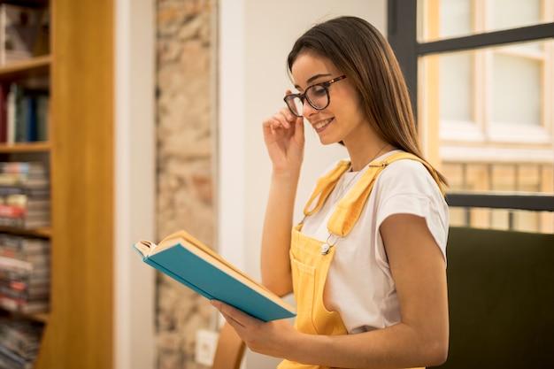 Привлекательная книга чтения молодой женщины в библиотеке