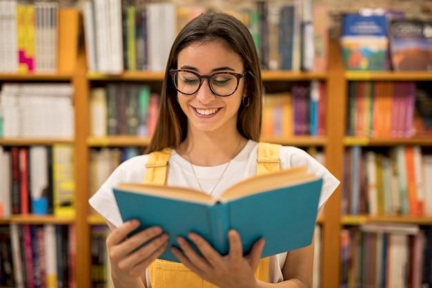 Подросток школьница в очках читает книгу