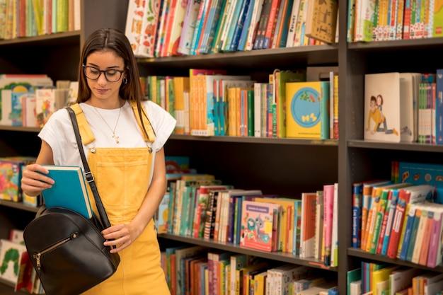 Стоящая школьница-подросток берет книгу из рюкзака