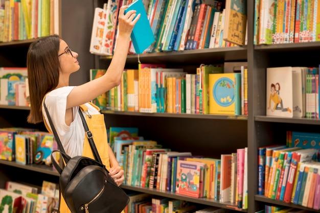 Школьница-подросток с рюкзаком собирает книгу с полки