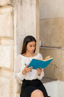 Молодая женщина читает книгу и держит очки