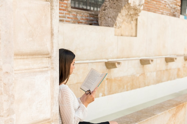 Молодая леди читает книгу и держит очки