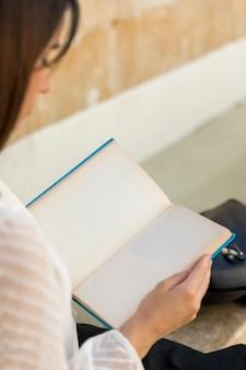 Женщина сидит и читает книгу в колледже