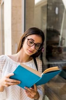 Молодая девушка в очках читает книгу возле окна