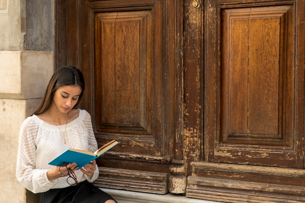 木製のドアのそばに座って読んでいる若い女性