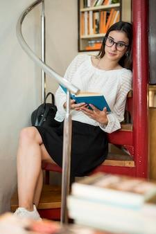 カメラ目線の本と座っている若い女性