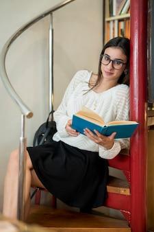 階段の上に座って本を持つかなりの学生