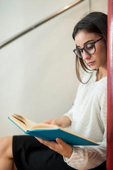 Подросток женщина читает книгу, сидя на лестнице в библиотеке