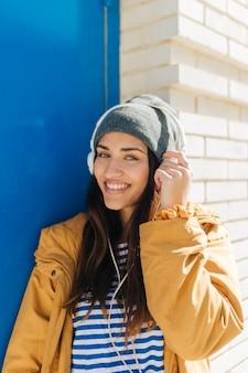 笑顔の女性がカメラを見て音楽を聴く