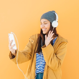 スマートフォンでビデオ通話中に挨拶する幸せな女性