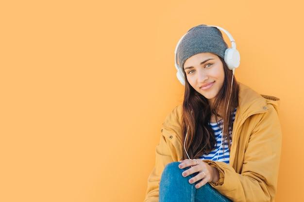 普通の黄色の背景の前に座っているカメラを見てヘッドセットを着ている女性