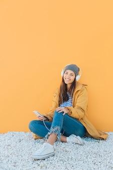 陽気な女性が黄色の表面に対して敷物の上に座ってのスマートフォンで音楽を聴く