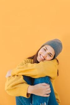 Привлекательная симпатичная женщина, глядя на камеру, сидя перед желтым фоном