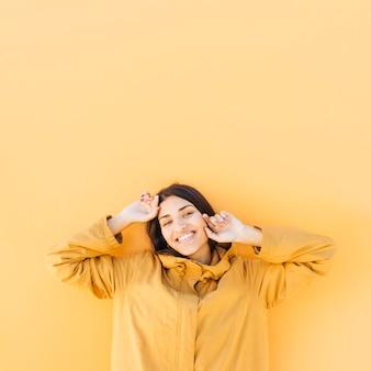 陽気な女性が普通の黄色を背景にポーズ