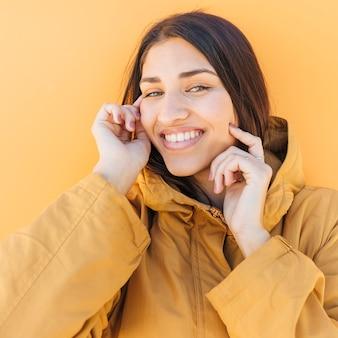 Счастливая женщина смотрит на камеру, касаясь ее щеки