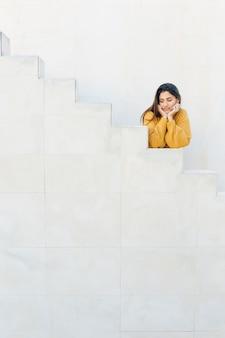 Женщина, опираясь на белые шаги, глядя в сторону