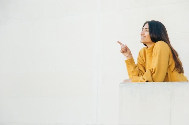 バルコニーに立って何かを指しているきれいな女性