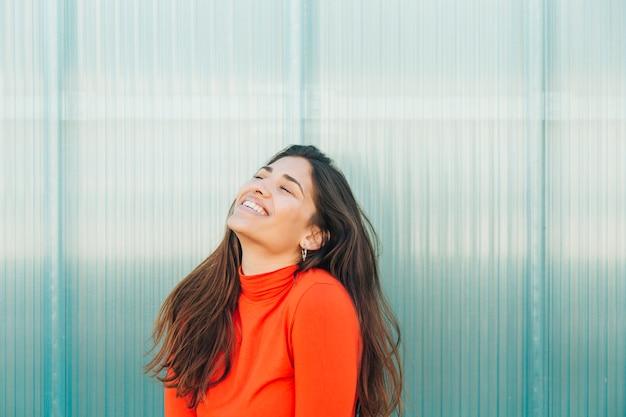 金属を背景にして笑っているきれいな女性