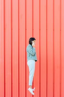 段ボールの赤い背景に対してジャンプしながら携帯電話で話している女性の側面図