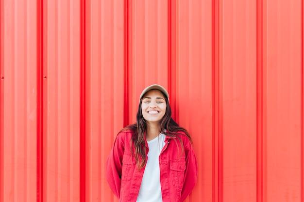 赤い段ボール背景に対して立っている笑顔の女性