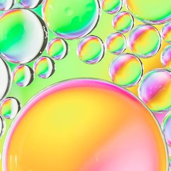 色とりどりの背景に水の中の抽象的な空気泡
