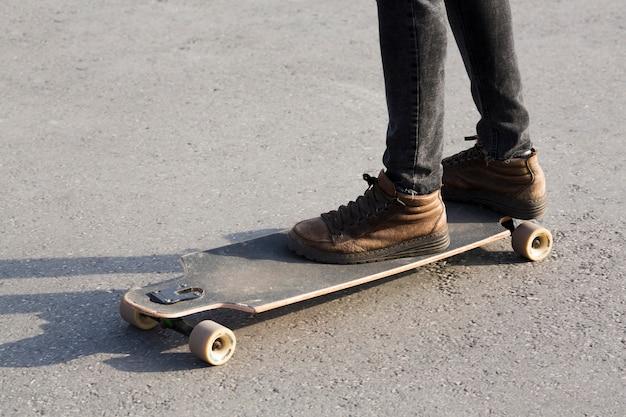 アスファルトの道路上のロングボードに男性の足