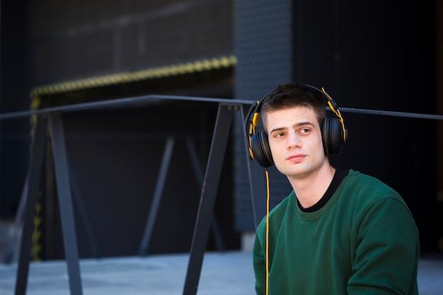 若い男がヘッドフォンで音楽を聴く